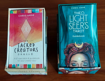 Open boxes of The Sacred Creators Oracle and LightSeers Tarot.